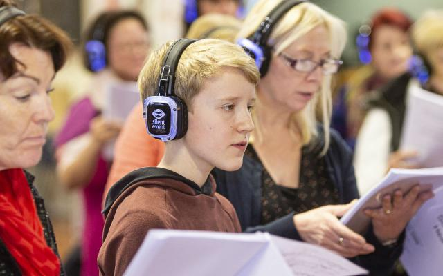 A young boy wears feedback headphones and holding sheet music, singing in a community choir