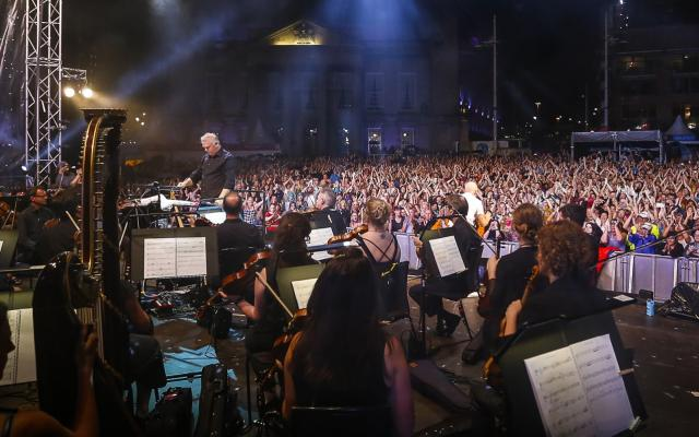 A large outdoor crowd seen from the back of an orchestra onstage, with a conductor leading them
