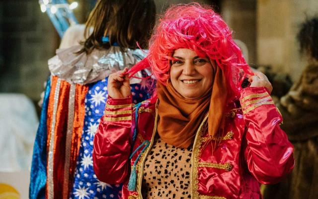 Lady in bright clothes tries on pink wig