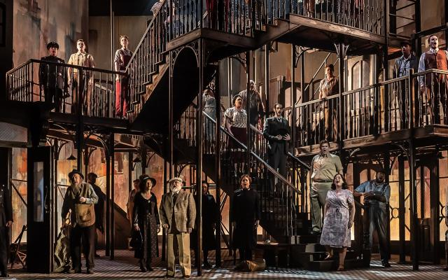 The cast of Street Scene crowd onto multiple levels of the 1940s tenement building set