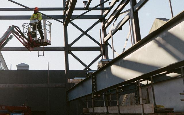 A workman on a hydraulic boom lift surrounded by an open steel frame, on a sunny day
