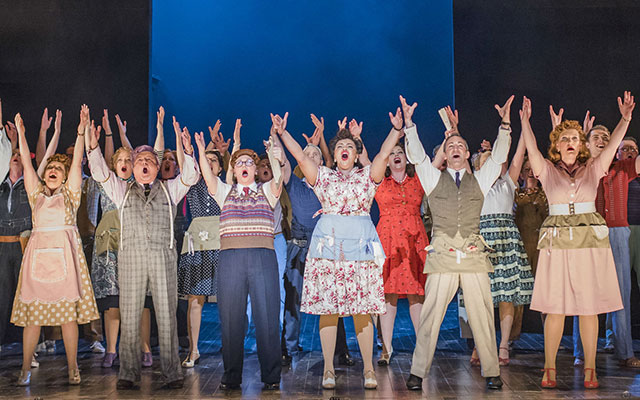 A group of people stand with arms flung high, up-lit and singing joyfully in colourful 50s style clothes
