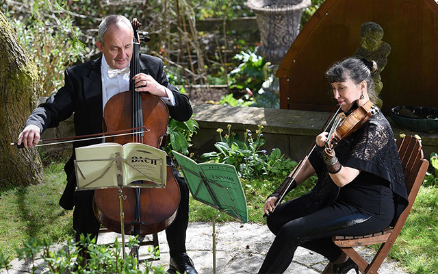 Two people playing the cello and violin in evening dress play in an idyllic garden setting