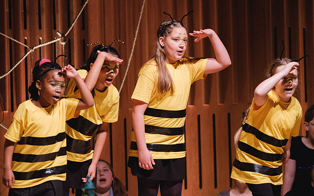 Children dressed in bee costumes performing as part of the Opera North Children's Choir