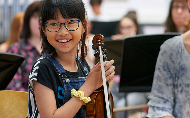 A girl smiles while holding a violin in a group ensemble