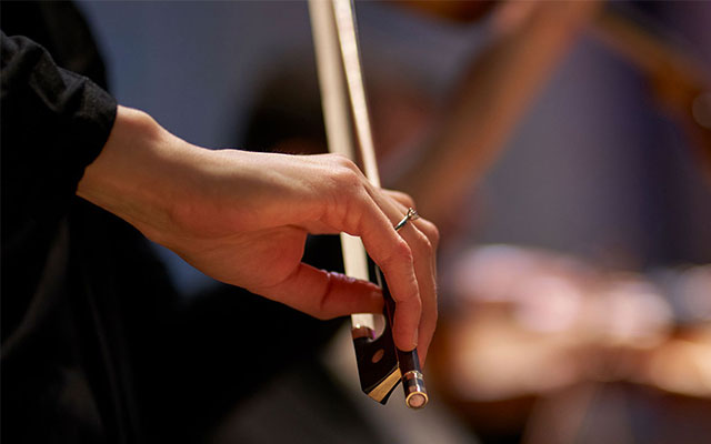 A woman's hand holds a violin bow