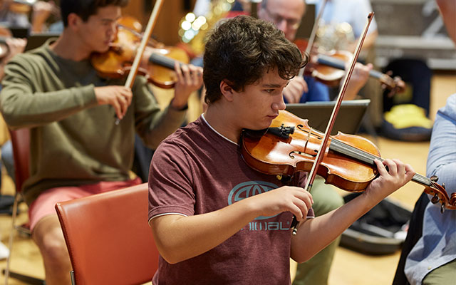 A boy plays a violin in a youth orchestra