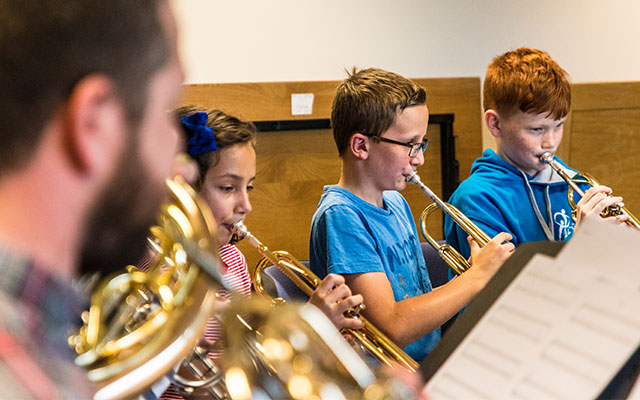 Young children play trumpets in a youth orchestra