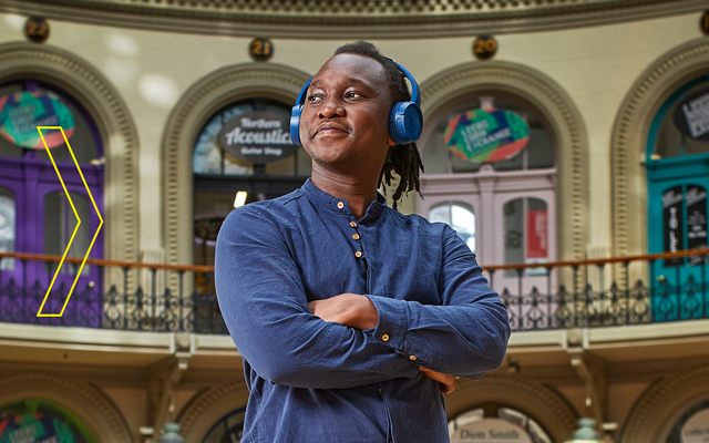 Musician, Abel Selaocoe stands with earphones on in the Corn Exchange
