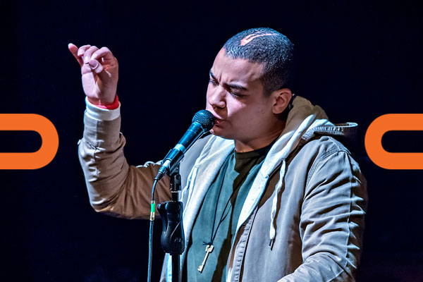 The rapper, Testament, sings into a microphone with his eyes closed and arm raised against a dark blue backdrop and orange graphics in the shape of chain links are overlaid