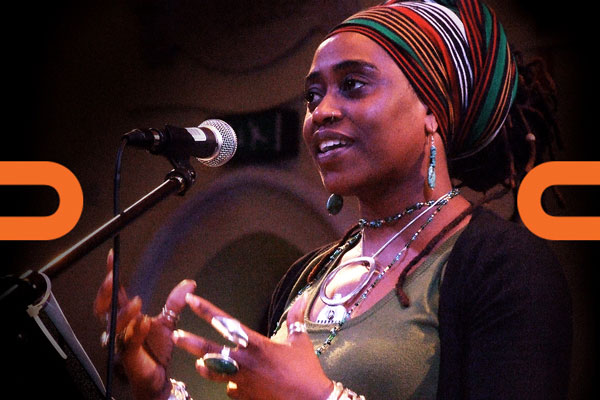 Spoken word artist, Khadijah Ibrahiim, speaks into a microphone with orange graphics in the shape of chain links overlaid