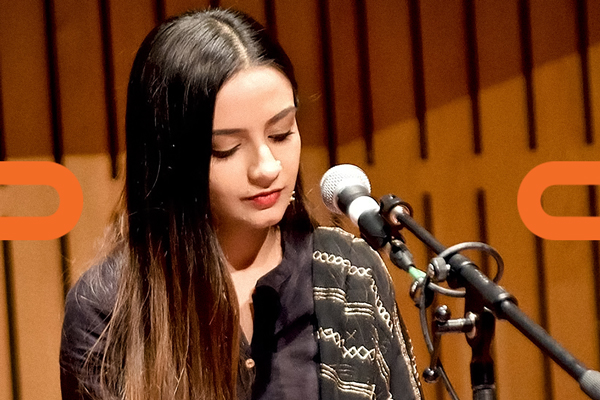 Keertan Kaur Rehal with a microphone in the Howard Assembly Room