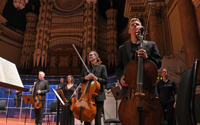 An orchestra stands with instruments in a grand concert hall setting at Leeds Town Hall