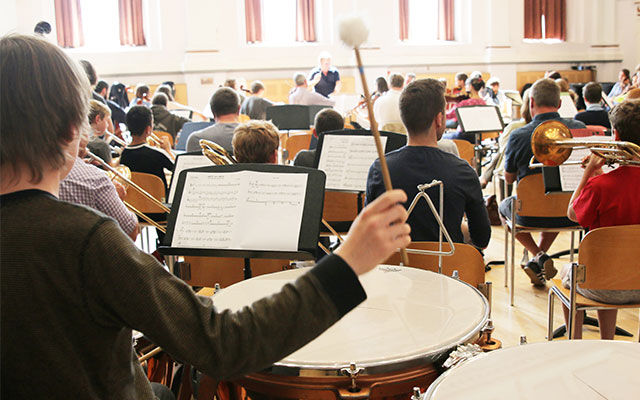 A boy beats a percussion drum in a youth orchestra