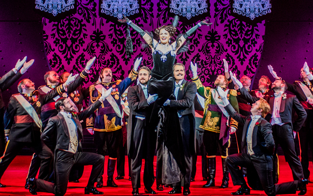 A lavish stage setting where woman lifts her arms up triumphantly while being held up by a group of people