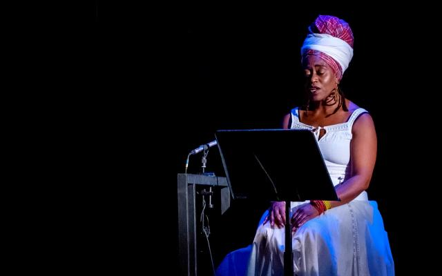 Poet Khadijah Ibrahiim, wearing a white dress and headscarf, performs seated on a darkened stage with a microphone and music stand