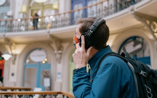 A man stands in Leeds Corn Exchange wearing headphones.