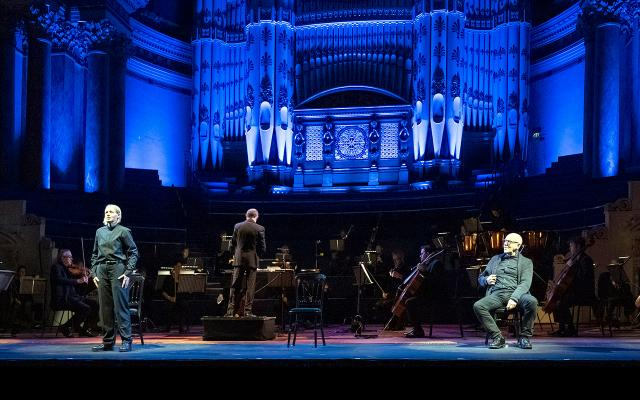 Singers in black stand on stage in front of an orchestra, and organ lit in blue.