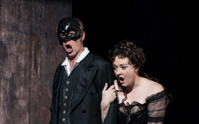 A man in a threatening black mask holds onto a woman in victorian dress in Opera North's Don Giovanni
