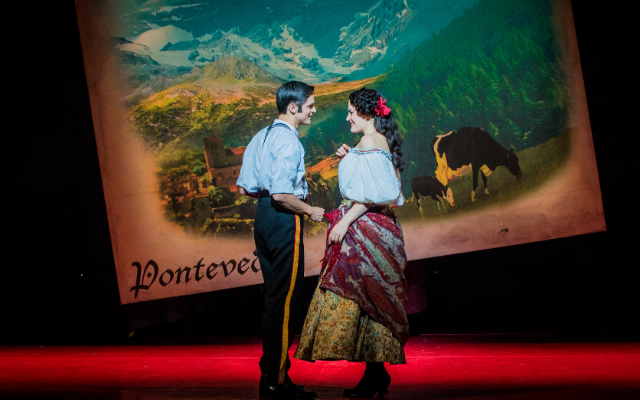 A man and woman sing to each other against an illustrated backdrop of mountains