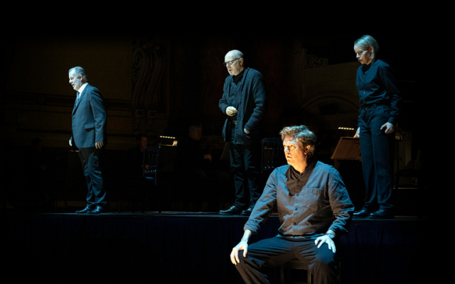 Four singers dressed in grey clothing perform on a darkly lit stage