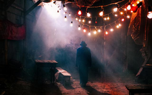 A shadowy figure wearing a hat walks through a darkly lit street with hanging lights above