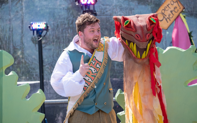 Man dressed in colourful costume sings outside on stage alongside a dragon puppet