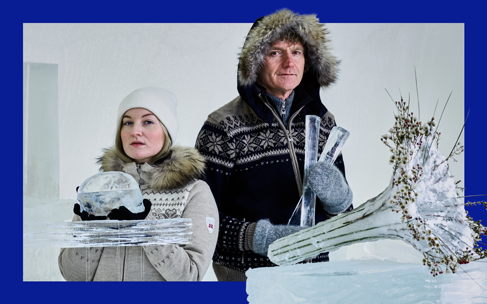 A man and woman dressed in cosy fur lined coats and wearing mittens stand behind a selection of instruments made of ice