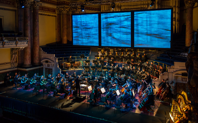 A full orchestra play in a warmly lit theatre space, blue projections can be seen on the back of the stage behind them