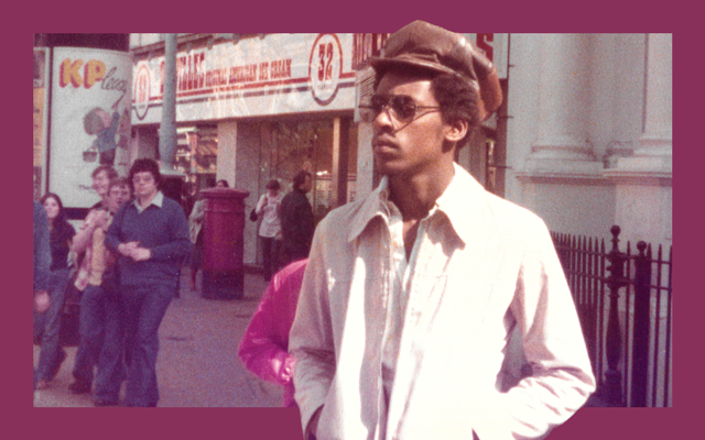 A man wearing a white jacket, brown hat and shaded sunglasses stands in a busy urban street