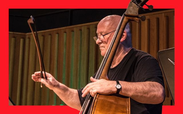 Bald man wearing glasses and a black T-shirt plays a Cello