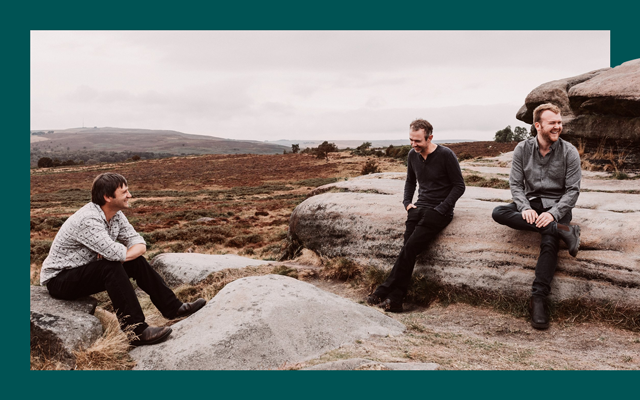 Three men dressed in casual clothing lean on rocks laughing with a view of sprawling fields and hills behind them