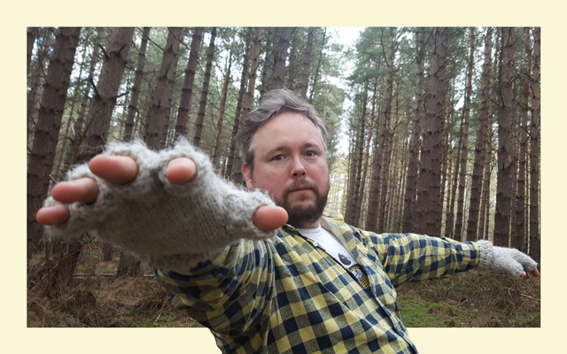 Man with grey hair and a brown beard, wearing yellow checked shirt and grey finger-less gloves stands in a woodland reaching towards the camera