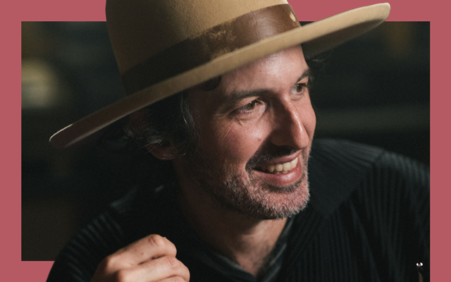 Man wearing a black shirt and brown wide rimmed hat smiles into the distance