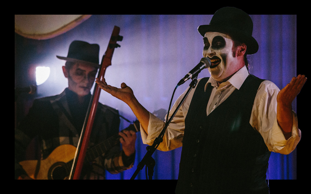 Two men wearing waistcoats and trilby hats with clown-like black and white face paint. One plays the guitar while the other laughs