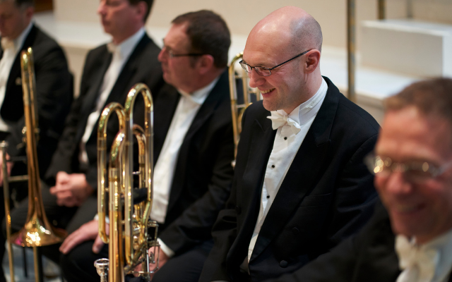 A group of men dressed in tailcoats smile whilst holding brass instruments