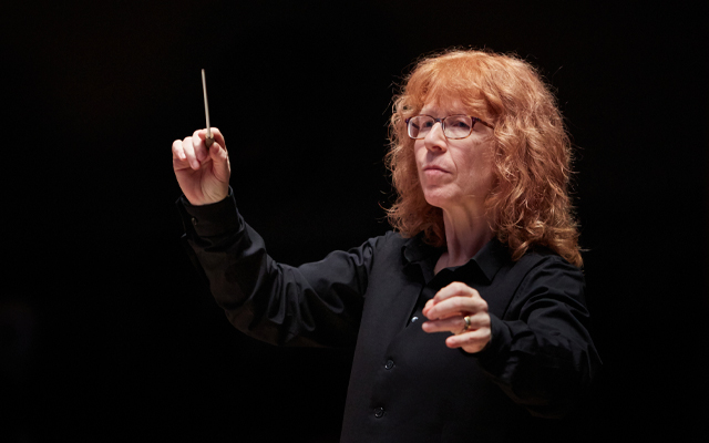 Woman with red hair and glasses holding a baton in the air