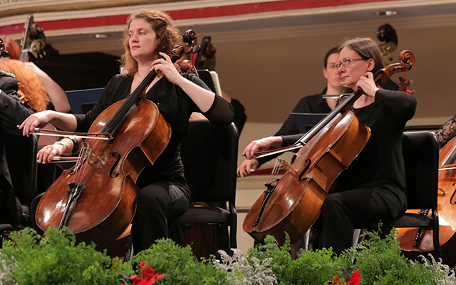 Three female cellists play in an orchestra