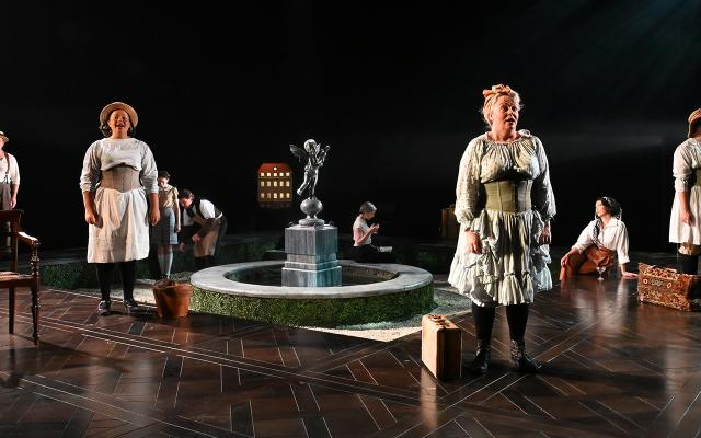 Three women and a man dresses in 18th century style under-garments stand equally distanced on a stage, singing. A number of props including a chair and a fountain can be seen behind them.
