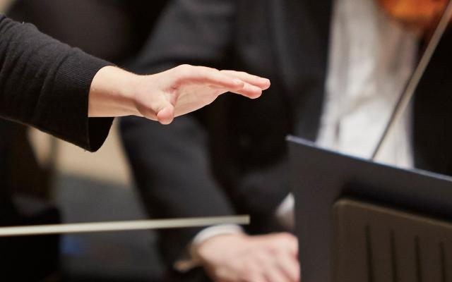 Female hands, one holding a conductor's baton, with a string section visible in the backgroundbaton,
