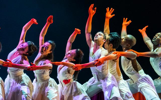 Male and female dancers in white robes with long red gloves each raise a hand aloft against a dark background