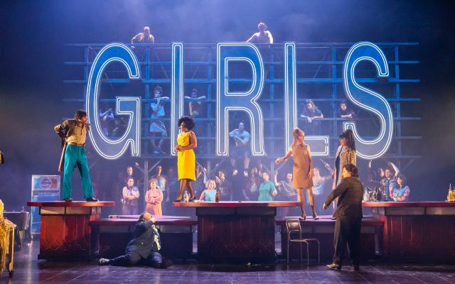 Patrons of a club walk the stage, a neon sign of the word 'GIRLS' can be seen in the background.