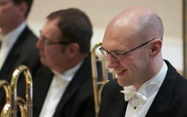 A smiling man in white tie and tailcoat with a trombone, surrounded by other brass players