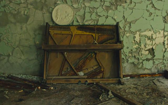 A ruined piano against a peeling light green wall, surrounded by debris