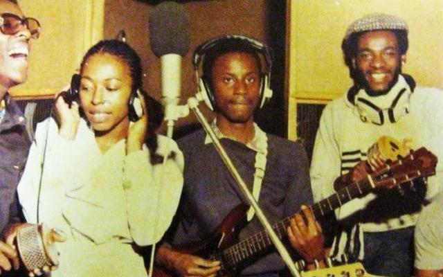 A reggae band and female singer gather around a microphone in a grainy vintage photo