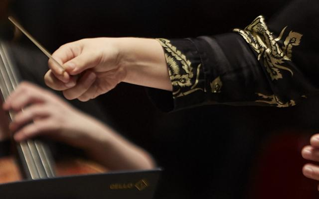 A woman's hands in ornate sleeves conducting an orchestra using a baton, with a cellist in the background