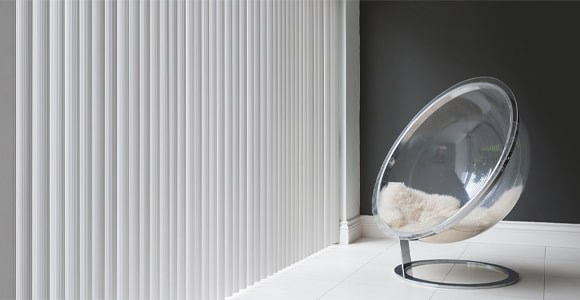 Rigid PVC vertical blinds create a modern and durable finish which is fire retardant and blackout