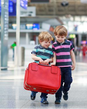 Child carrying a suitcase