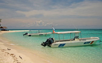 Speedboats in the shallow turquoise water and white beach beside