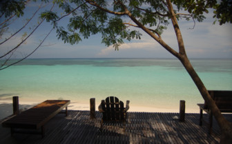 View from the trees out to white sand and turquoise water